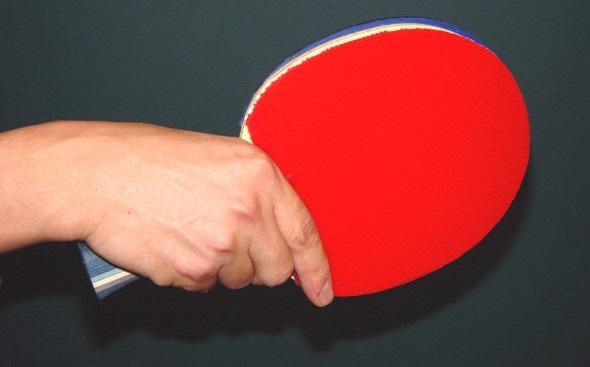 Mão segurando raquete